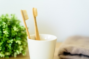 Two wooden toothbrushes in ceramic cup at bathroom.